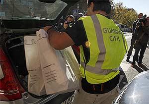 Un agente de la Guardia Civil mete documentación incautada en Urbanismo en un coche. (EFE)