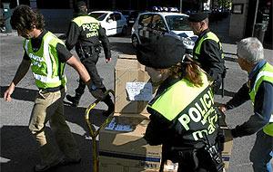 Policías y guardia civiles portan documentación incautada en la Gerencia de Medio Ambiente. (Pedro Blasco)