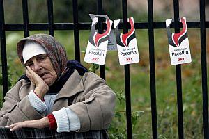 Una mujer albanesa, sentada junto a varios carteles electorales. (Foto: EFE)