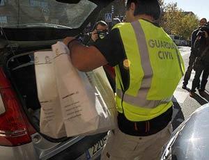 Un guardia civil mete documentación incautada en los registros de sedes municipales de la pasada semana. (EFE)