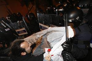 Un manifestante se enfrenta a un Mosso d'Esquadra que franquea la calle de la Librería Europa (Foto: Santi Cogolludo)