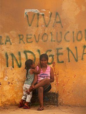 Dos niñas indígenas en Santa Cruz, junto a una pintada en apoyo a la revolución. (Foto: AP)