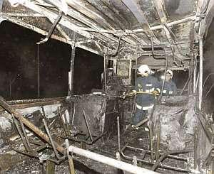 Los bomberos entran dentro del autobús, que está completamente calcinado. (Foto: EFE)