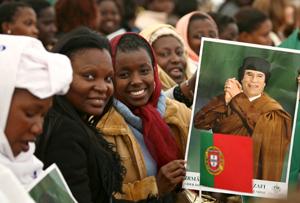 Mujeres sujetando una foto de Gaddafi, ayer, en Lisboa. (Foto: EFE)