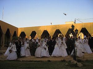 Las parejas posan en los jardines del hotel Palestine mientras sobrevuela un Apache. (Foto: Mónica G. Prieto)