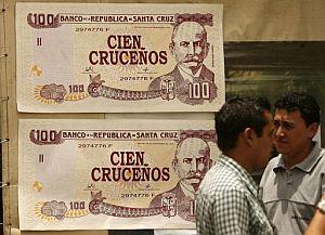 """Dos hombres caminan este 10 de diciembre de 2007 frente a unos billetes de """"cien pesos cruceños"""", diseñados por un artista plástico boliviano. (Foto: EFE)"""
