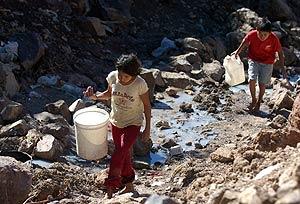 Unos niños recogen agua en Tegucigalpa, Honduras, uno de los países más afectados por los desastres. (Foto: EFE)