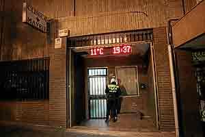 Un agente municipal en la puerta de la clínica Mayrit, en la calle Toledo. (Foto: Diego Sinova)