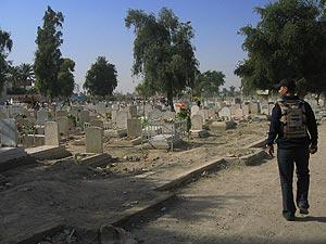 Un miliciano de Al Sahwa pasea ante el 'cementerio de los mártires' de Adhamiya. (Mónica G. Prieto)