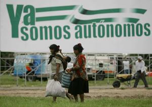 Unas mujeres indígenas caminan en Santa Cruz frente a un cartel en favor de la independencia, (Foto: AP)