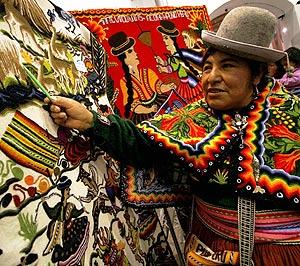 Una indígena, junto a artesanía boliviana. (EFE)