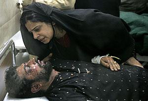Una mujer con uno de los familiares heridos en el atentado que acabó con Bhutto. (Foto: EFE)