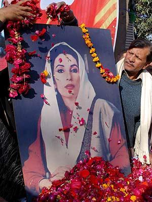 Seguidores de la ex primera ministra depositan pétalos de flores junto a su retrato. (Foto: EFE)