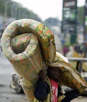 Un niño traslada un colchón en su huida de la ciudad de Kisumu. (Foto: REUTERS)