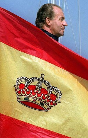 Don Juan Carlos, en una imagen de archivo con la bandera nacional en primer término. (Foto: EFE)
