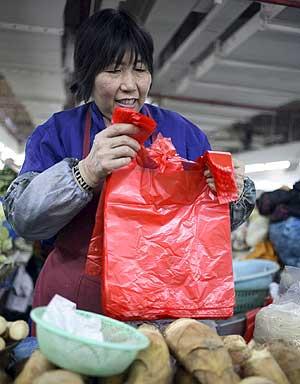 Una tendera china se dispone a despachar en una bolsa de plástico. (Foto: EFE)