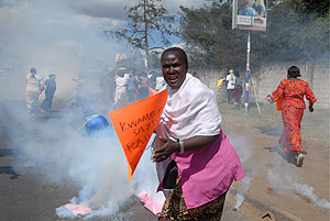 Una partidaria de la oposición corre mientras la policía lanza bombas lacrimógenas en Nairobi. (Foto: EFE)
