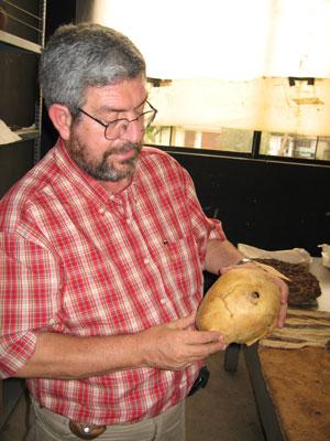 El arqueólogo Guillermo Cock muestra el cráneo del rebelde inca con un impacto de una bala. (Foto: Universidad Católica de Lima)