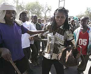 Varios hombres rodean a una mujer de una etnia rival. (Foto: AP) MÁS FOTOS