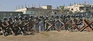 Decenas de policías equipados con cascos y escudos antidisturbios vigilan un tramo de frontera. (Foto: AP)