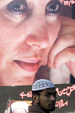 Un paquistaní pasa por delante de un cartel con la imagen de Bhutto. (Foto: AFP)