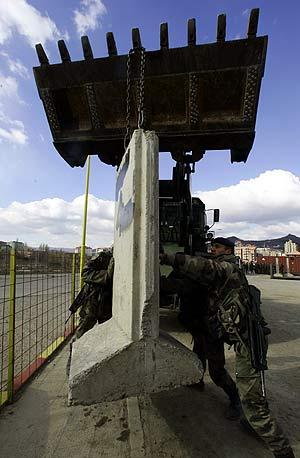 Miembros de la KFOR montan un control entre la zona que separa a serbios y albaneses junto al río Ibar. (AP)