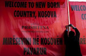 Un albanés cuelga un gran cartel que reza 'Bienvenido a un país recién nacido, Kosovo' en Pristina. (Foto: EFE)