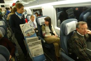 Una de las azafatas del primer AVE Barcelona-Madrid reparte prensa entre los pasajeros. (Foto: Quique García)