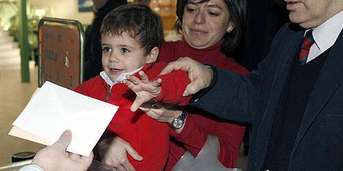 Un niño entrega el voto de su madre en Madrid. (Foto: EFE)