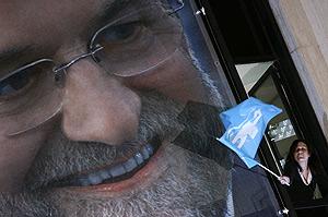 Una simpatizante ondea la bandera del PP en la sede de Génova. (Foto: EFE)