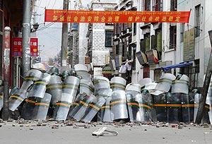 Guardias de seguridad chinos se parapetan de los manifestants en Lhasa. (Foto: REUTERS)
