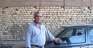 Majid Kasem Yusef, conductor chií, ante su vehículo.