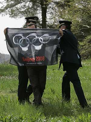 Un activista muestra una bandera en la que los aros olímpicos han sido sustituidos por esposas durante el encendido de la llama. (Foto: AP)