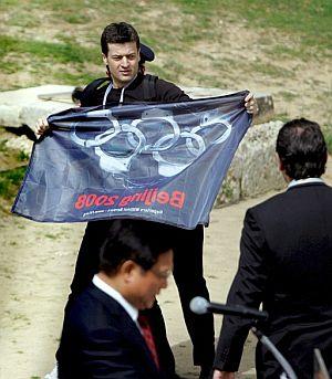 Jean François Julliard muestra una bandera en la que los aros olímpicos han sido sustituidos por esposas. (Foto: EFE)