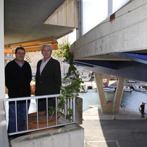 Los vecinos más afectados por el puente posan en un balcón con la infraestructura sobre sus cabezas. (Foto: Cati Cladera)