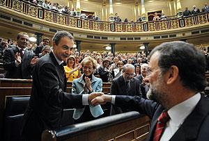Rajoy felicita a Zapatero, bajo los aplausos del resto de los diputados. (Foto: AP)