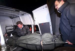 Miembros del servicio funerario introducen el cadáver de la víctima en el coche. (Foto: EFE)