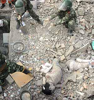 Unos soldados retiran escombros con sus propias manos y una pala junto a dos cadáveres semi enterrados. (Foto: AFP)