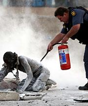 Un policía ayuda a una persona a quien prendieron fuego.