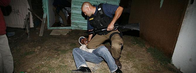Un policía detiene a un sospechoso en los alrededores de Ciudad del Cabo. (Foto: AFP)