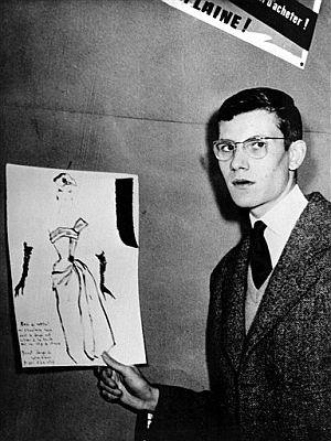 Saint-Laurent posa, en diciembre de 1954, con el diseño de un vestido de cóctel que le dio su primer premio en 1953. (Foto: AP)