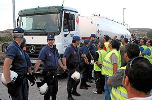 La policía escolta, el martes, un camión cisterna en Alicante. (Foto: El Mundo)