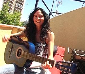 La actriz tocando la guitarra en la terraza.