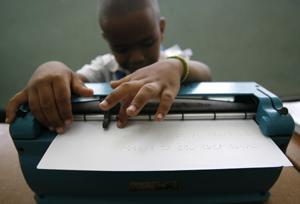 Un muchacho con discapacidad visual comprueba con sus yemas lo que ha escrito en braille. (Foto: REUTERS).