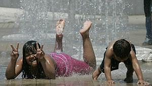 Dos niños con el agua de una fuente en Bilbao. (Foto: Mitxi)