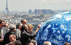 Pachauri firma un globo terráqueo en el segundo día de la reunión de ministros en París. (Foto: AFP)