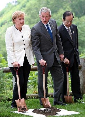Merkel y Bush plantan un árbol, durante la Cumbre. (Foto: AP)