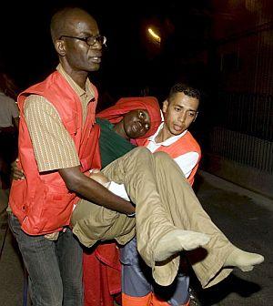 Unos voluntarios transportan a una de los inmigrantes que han perdido a sus hijos cuando se dirigían a España la semana pasada. (Foto: EFE)