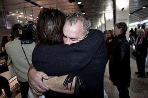 Un pasajero se abraza con su esposa al llegar al aeropuerto de Melbourne, horas después del susto vivido en Manila. (Foto: AP)