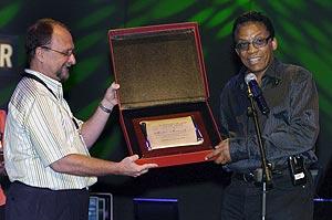 El director del festival Alberto Nieto, hace entrega de una placa conmemorativa a toda su carrera, al pianista y compositor de jazz Herbie Hancock (Foto: EFE)